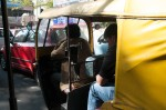 John sits in traffic, in autorickshaw. Can you see Pam in the mirror?