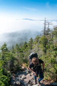 Photo of a hiker with an undercast sky in the background, Mount Moosilauke looming above.
