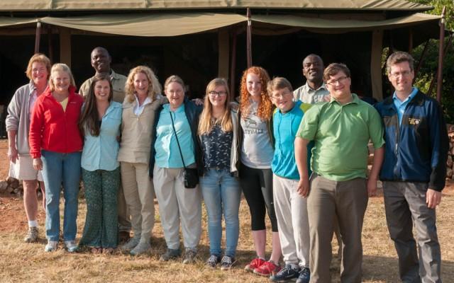 Safari group photo: Peggy, Amy, Erin, Doe, Pam, Mara, Isabel, Andy, John, David; with guides Robert and Freddy in back. At Serengeti East nyumba, Enashiva Reserve, last morning of the safari.