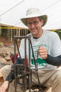 Dave uses an antique boring machine to drill mortises in one of the king posts.